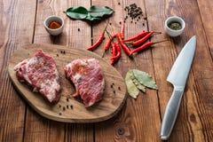 Vlees met één of andere specerij op keukenlijst stock afbeelding
