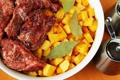 Vlees met aardappels in een witte plaat voor het koken Stock Foto