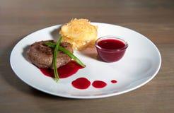 Vlees met gebraden aardappels en salade gekleed met saus Stock Foto's