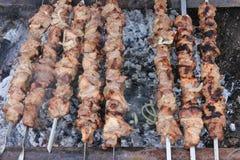 Vlees op vleespennen die over houtskool worden geroosterd Stock Fotografie