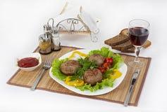 Vlees van rundvlees, ronde rhizol Ronde vleeskoteletten met greens, tomaten en een glas wijn Nuttig en smakelijk ontbijt Stock Foto