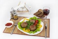 Vlees van rundvlees, ronde rhizol Ronde vleeskoteletten met greens, tomaten en een glas wijn Nuttig en smakelijk ontbijt Royalty-vrije Stock Fotografie