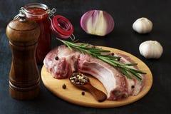 Vlees, varkensvleesentrecôte met rozemarijn, ui, knoflook en pimentbes Stock Fotografie