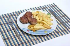 Vleesballetjes met frieten stock foto