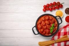 Vleesballetjes in tomatensaus met kruiden en basilicum in een pan en kersentomaten op een witte houten raad royalty-vrije stock afbeeldingen