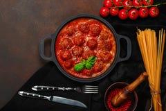 Vleesballetjes in tomatensaus met kruiden, kersentomaten, deegwaren en basilicum in een pan op roestige bruine achtergrond stock foto