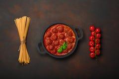Vleesballetjes in tomatensaus met kruiden, kersentomaten, deegwaren en basilicum in een pan op roestige bruine achtergrond royalty-vrije stock fotografie