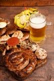 Vleesbarbecue op de lijst wordt geplaatst die Worsten, varkensvlees, paddestoelen, rundvlees, sausen, groenten in het zuur Biersn royalty-vrije stock afbeeldingen