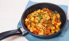 Vleeshutspot met aardappels, peper, ui en wortel in een pan Stock Fotografie