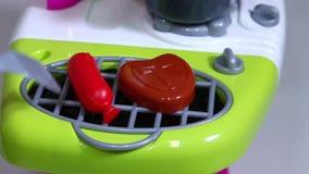 Vleeslapje vlees en worst bij stuk speelgoed de plastic grill wordt geroosterd die