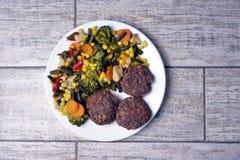 Vleespasteitjes met groenten op een witte plaat op een grijze achtergrond stock fotografie