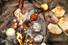 Vleespennen die op kampbrand rosting. Royalty-vrije Stock Fotografie