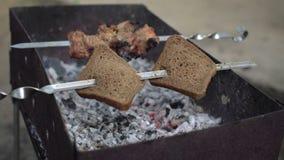 Vleespennen met brood en kebab die bij de grill voorbereidingen treffen stock videobeelden