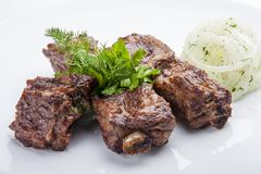Vleespennen van varkensvleesribben met uien stock afbeeldingen