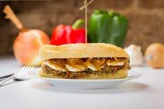 Vleessandwich met zoete ui en geitkaas stock fotografie