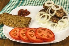 Vleesworsten met tomaat, ui, saus en brood Royalty-vrije Stock Foto's