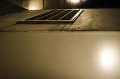 Vlekken van gele lichten buiten een grijs gebouw, op de stedelijke straat van de stad stock afbeelding