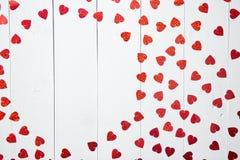 Vlentines dagsammansättning Hjärta formade paljetter som förlades på den vita trätabellen arkivfoton