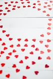 Vlentines dagsammansättning Hjärta formade paljetter som förlades på den vita trätabellen arkivbild