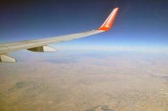 Vleugel die van vliegtuig in de hemel op een duidelijke dag vliegen stock afbeeldingen