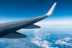 Vleugel die van vliegtuig over wolken en bergen vliegen Royalty-vrije Stock Afbeeldingen