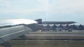 Vleugel van een een baan en draai van de vliegtuigtaxi rond in Luchthaven, schot van het venster van het vliegtuig stock footage