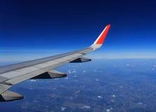 Vleugel van een vliegtuig dat boven de wolken vliegt royalty-vrije stock afbeelding