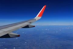 Vleugel van een vliegtuig dat boven de wolken vliegt royalty-vrije stock foto's