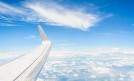 Vleugel van een vliegtuig dat boven de wolken vliegt Stock Foto's