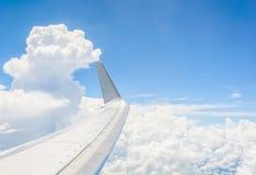 Vleugel van een vliegtuig dat boven de wolken vliegt Stock Afbeelding