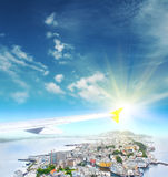 Vleugel van een vliegtuig die boven de stad bij zonsopgang vliegen Stock Foto's