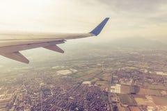 Vleugel van een vliegtuig die boven steden en dorpen vliegen royalty-vrije stock foto's