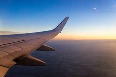 Vleugel van het luchtvliegtuig op het overzees van de hemelachtergrond van de wolkenzonsondergang Stock Afbeeldingen
