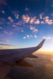 Vleugel van het luchtvliegtuig op het overzees van de hemelachtergrond van de wolkenzonsondergang Royalty-vrije Stock Afbeelding