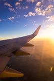 Vleugel van het luchtvliegtuig op het overzees van de hemelachtergrond van de wolkenzonsondergang Stock Foto