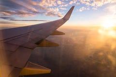 Vleugel van het luchtvliegtuig op het overzees van de hemelachtergrond van de wolkenzonsondergang Royalty-vrije Stock Foto