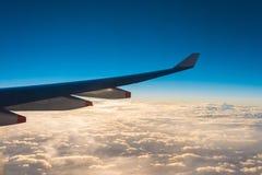 Vleugel van het luchtvliegtuig op het overzees van de hemelachtergrond van de wolkenzonsondergang Royalty-vrije Stock Afbeeldingen