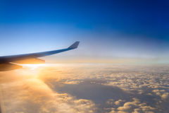Vleugel van het luchtvliegtuig op het overzees van de hemelachtergrond van de wolkenzonsondergang Stock Foto's