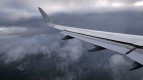 Vleugel van landende vliegtuig of straal op achtergrond van de onweers de grijze hemel stock footage