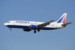 Vliegend Boeing 737-400 van het bedrijftransaero (van EI-CZK) Luchtvaartlijnen op de achtergrond van blauwe hemel Stock Foto's