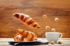 Vliegend croissant met koffie stock foto's