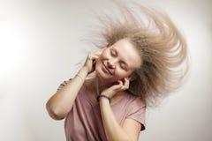 Vliegend dansend haar jonge charmante vrouw met donsachtig haar in oortelefoons stock afbeelding