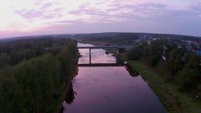 Vliegend over de rivier Mologa in de avond, aan de brug bij het dorp stock videobeelden