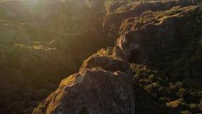 Vliegend over de scherpe rotsen met oud weinig vesting in Georgië stock footage