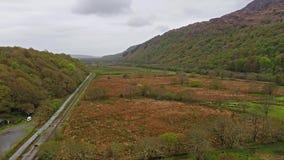 Vliegend over gebieden, rivier en spoorwegspoor tussen twee bergen stock footage