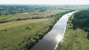 Vliegend over het dorp, de gebieden, de rivier en de bossen Mooie vogel` s-oog mening bij het hangen van oude brug over de rivier stock videobeelden