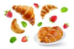 Vliegende croissants met aardbeien en geïsoleerde muntbladeren Stock Afbeelding