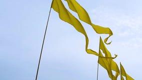 Vliegende gele banners op vlaggestokken op hemelachtergrond tijdens een openluchtgebeurtenis stock videobeelden