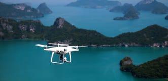 Vliegende Hommelcamera of UAV in de blauwe hemel met oceaan en eiland Royalty-vrije Stock Foto's