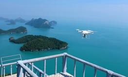 Vliegende Hommelcamera of UAV in de blauwe hemel met oceaan en eiland Royalty-vrije Stock Afbeelding